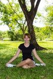 Yoga di felicità delle giovani donne con fornito di gambe trasversale Fotografia Stock