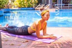 Yoga di formazione della donna al tramonto vicino alla piscina fotografia stock