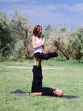 Yoga di mattina nel parco di verde della città Una bella coppia tiene una classe di yoga Immagini Stock Libere da Diritti