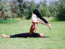 Yoga di mattina nel parco di verde della città Una bella coppia tiene una classe di yoga Fotografie Stock