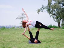 Yoga di mattina nel parco di verde della città Una bella coppia tiene una classe di yoga Immagini Stock