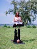 Yoga di mattina nel parco di verde della città Una bella coppia tiene una classe di yoga Immagine Stock