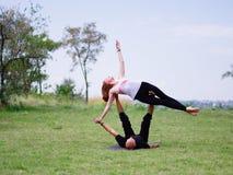 Yoga di mattina nel parco di verde della città Una bella coppia tiene una classe di yoga Fotografia Stock