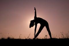 Yoga di posa del triangolo con la giovane donna profilata Fotografie Stock Libere da Diritti