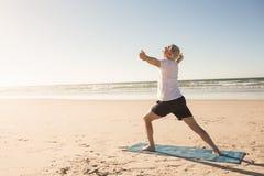 Yoga di pratica attiva dell'uomo senior alla spiaggia Fotografia Stock