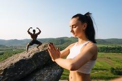 Yoga di pratica caucasica athlethic sexy del culturista della donna e dell'afroamericano delle coppie della corsa mista insieme A Fotografia Stock