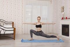 Yoga di pratica che allunga sulla stuoia, posa della bella giovane donna del guerriero Fotografia Stock Libera da Diritti