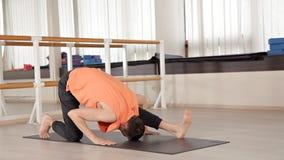Yoga di pratica di yoga dei giovani di sport, esercitantesi, abbigliamento di sport, il concetto di benessere allo studio di yoga video d archivio