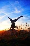 Yoga di pratica del giovane ed allungare su una roccia alla luce di tramonto Immagine Stock