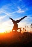 Yoga di pratica del giovane ed allungare su una roccia alla luce di tramonto Immagine Stock Libera da Diritti