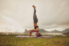 Yoga di pratica del headstand della donna di forma fisica all'aperto Immagini Stock