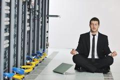 Yoga di pratica dell'uomo di affari alla stanza del servizio rete Immagine Stock