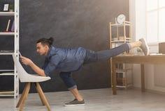 Yoga di pratica dell'uomo flessibile nel luogo di lavoro Immagini Stock