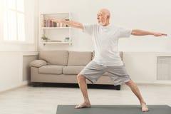 Yoga di pratica dell'uomo senior all'interno immagini stock libere da diritti