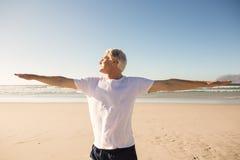 Yoga di pratica dell'uomo senior alla spiaggia Immagine Stock
