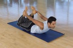 Yoga di pratica dell'uomo sulla stuoia Fotografia Stock