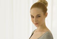 Yoga di pratica della bella donna bionda che allunga a casa nella tuta grigia, colpo del ritratto, sorridente Fotografia Stock Libera da Diritti