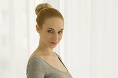 Yoga di pratica della bella donna bionda che allunga a casa nella tuta grigia, colpo del ritratto, sorridente Immagine Stock