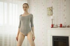 Yoga di pratica della bella donna bionda che allunga a casa nella tuta grigia e nei calzini rosa Immagine Stock Libera da Diritti