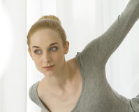Yoga di pratica della bella donna bionda che allunga a casa nella tuta grigia e nei calzini rosa Immagini Stock Libere da Diritti