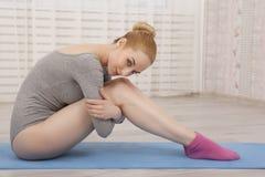 Yoga di pratica della bella donna bionda che allunga a casa sulla stuoia blu in tuta grigia ed in calzini rosa Immagine Stock Libera da Diritti