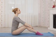 Yoga di pratica della bella donna bionda che allunga a casa sulla stuoia blu in tuta grigia ed in calzini rosa Fotografia Stock Libera da Diritti