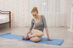 Yoga di pratica della bella donna bionda che allunga a casa sulla stuoia blu in tuta grigia ed in calzini rosa Fotografie Stock Libere da Diritti