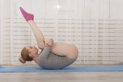 Yoga di pratica della bella donna bionda che allunga a casa sulla stuoia blu in tuta grigia ed in calzini rosa Fotografie Stock