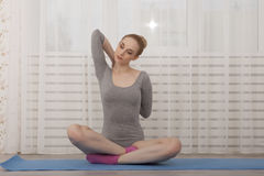 Yoga di pratica della bella donna bionda che allunga a casa sulla stuoia blu in tuta grigia ed in calzini rosa Immagini Stock Libere da Diritti