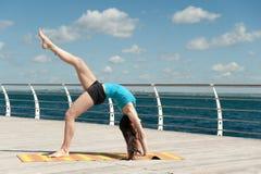 Yoga di pratica della bella donna sul mare fotografia stock libera da diritti