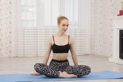 Yoga di pratica della bella giovane donna a casa sulla stuoia - meditazione Immagini Stock Libere da Diritti