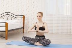 Yoga di pratica della bella giovane donna a casa sulla stuoia - meditazione Fotografia Stock