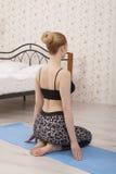 Yoga di pratica della bella giovane donna che allunga a casa sulla stuoia Fotografia Stock Libera da Diritti