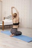Yoga di pratica della bella giovane donna che allunga a casa sulla stuoia Fotografie Stock