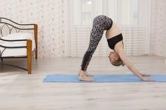 Yoga di pratica della bella giovane donna che allunga a casa sulla stuoia Immagine Stock