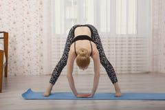 Yoga di pratica della bella giovane donna che allunga a casa sulla stuoia Immagini Stock Libere da Diritti