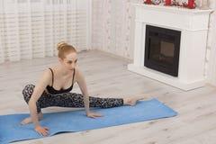 Yoga di pratica della bella giovane donna che allunga a casa sulla stuoia Fotografia Stock