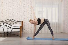 Yoga di pratica della bella giovane donna che allunga a casa sulla stuoia Immagini Stock