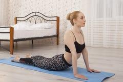 Yoga di pratica della bella giovane donna che allunga a casa sulla stuoia - posa della cobra Fotografia Stock Libera da Diritti
