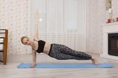 Yoga di pratica della bella giovane donna che allunga a casa sulla stuoia - sponda Fotografia Stock