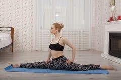 Yoga di pratica della bella giovane donna che allunga sulla stuoia che fa le spaccature Fotografia Stock Libera da Diritti