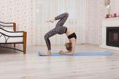 Yoga di pratica della bella giovane donna, eseguente ponte pieno a casa, vista laterale Fotografia Stock Libera da Diritti