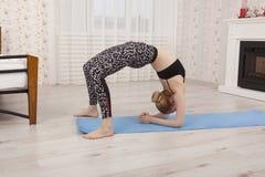 Yoga di pratica della bella giovane donna, eseguente ponte pieno a casa, vista laterale Immagine Stock