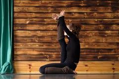 Yoga di pratica della bella giovane donna sportiva, facente posa dell'airone, Krounchasana fotografie stock