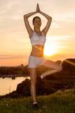 Yoga di pratica della bella ragazza nel tramonto Fotografia Stock Libera da Diritti