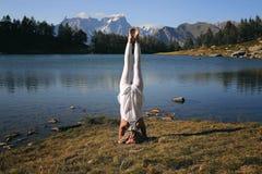 Yoga di pratica della donna alla montagna lakeshore immagine stock