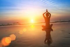 Yoga di pratica della donna alla spiaggia durante il tramonto distendasi Immagini Stock