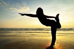 Yoga di pratica della donna asiatica della siluetta Fotografia Stock