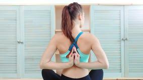 Yoga di pratica della donna attiva degli Yogi che si siede con il namaste dietro il colpo medio posteriore video d archivio