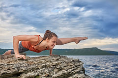 Yoga di pratica della donna in buona salute sulla roccia contro bello paesaggio con il fiume Fotografia Stock